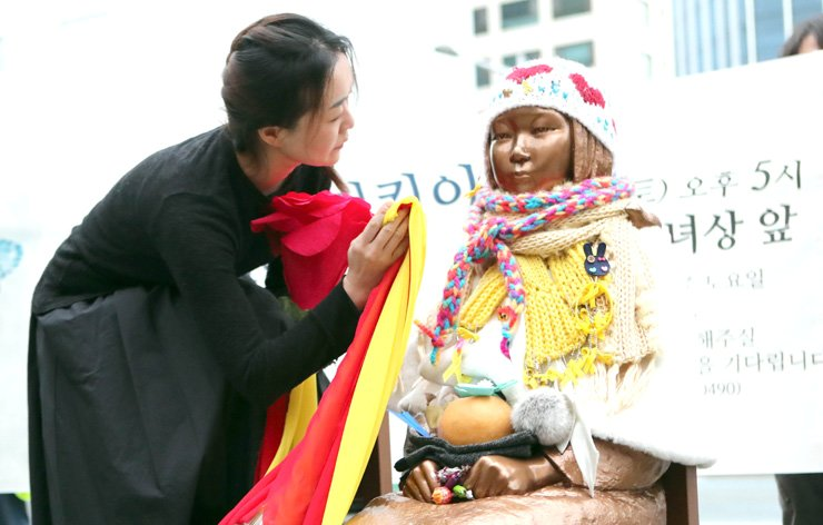 An activist wipes dust off the statue of a girl symbolzing former Korean sex slaves during the 1910-45 Japanese colonial rule outside the Japanese consulate in Busan on Feb. 4. / Yonhap
