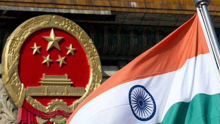 The Indian national flag flies next to the Chinese national emblem outside the Great Hall of the People in Beijing. The two nations could be on the brink of war.