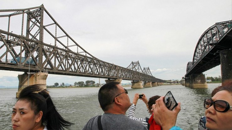 Tourists at the bridge linking North Korea and China (left) across the Yalu River.
