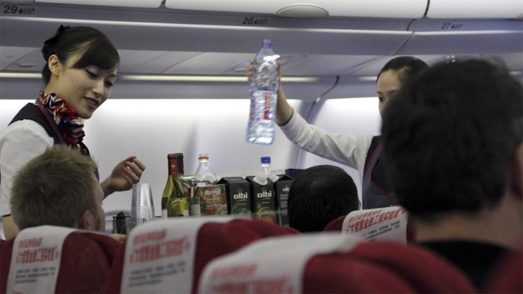 Flight attendants serve a meal on a flight. Sudden turbulence when you're manning a 90kg food cart is one of the worst nightmares for cabin crew.