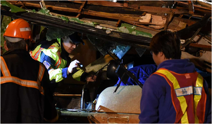 Rescuers work at the site of a bus accident in Taipei, southeast China's Taiwan, Feb. 14, 2017.