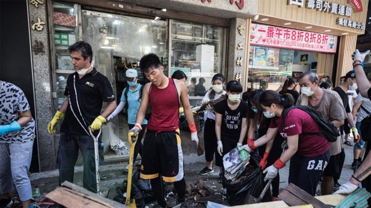 Local residents clean debris and rubbish on a street in the aftermath of Typhoon Hato in Macau.