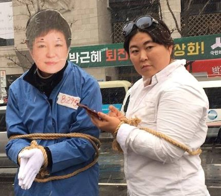Street artists put on costumes and use props to pretend as President Park Geun-hye (left) and her longtime friend and influence-peddler Choi Soon-sil. / Courtesy of Twitter