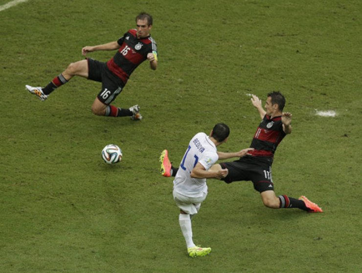 United States' Alejandro Bedoya, below, takes a shot against Germany's Philipp Lahm and Miroslav Klose, right, during their group G World Cup match in Recife, Brazil, Thursday. / AP-Yonhap