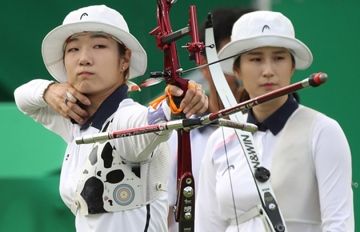 South Korea captured the gold medal in women's archery team competition at the Rio de Janeiro Olympics on Sunday. Choi Mi-sun, left, takes aim while Ki Bo-bae awaits. / Yonhap