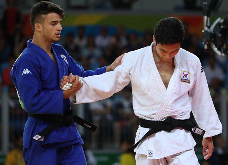 Italian judoka Fabio Basile, left, comforts South Korea's An Ba-ul after winning the men's -66kg final at the Rio de Janeiro Olympics, Sunday. / Yonhap