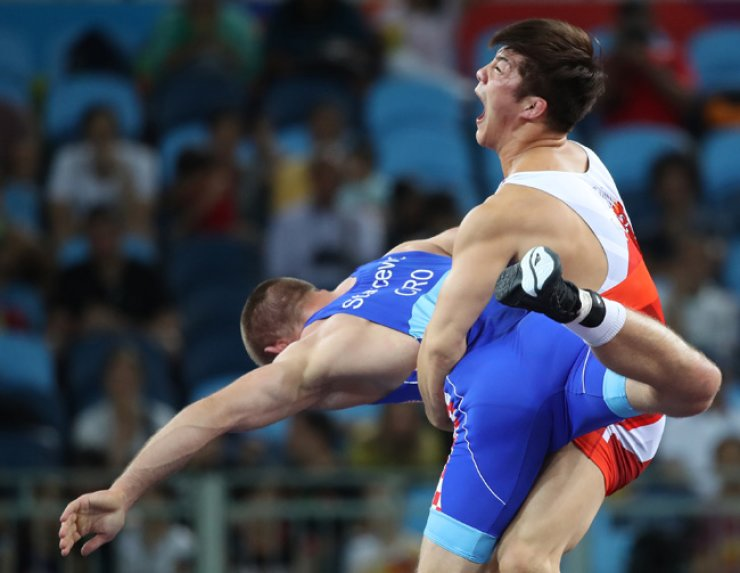 South Korean Greco-Roman wrestler Kim Hyeon-woo lifts up Croatia's Bozo Starcevic in the 75-kg bronze medal match at the Rio de Janeiro Olympics, Sunday. Kim beat Starcevic 6-4. / Yonhap