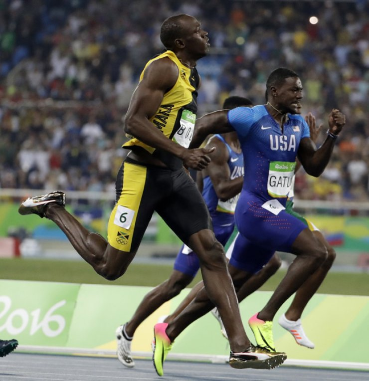 Jamaican sprinter Usain Bolt, left, finishes first in the final 100-meter heat at the Rio de Janeiro Olympics on Sunday with American Justin Gatlin in a close second, finishing in 9.81 seconds. Bolt won the gold and became the first sprinter to win three straight Olympic 100-meter titles. / AP-Yonhap