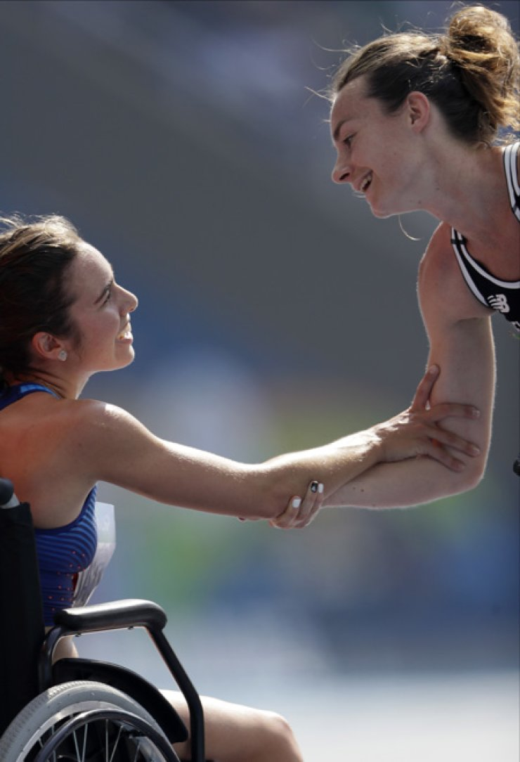 Nikki Hamblin of New Zealand and Abbey D'Agostino of the U.S. shake hands after competing in a heat of the 5000m in Rio de Janeiro. / AP-Yonhap