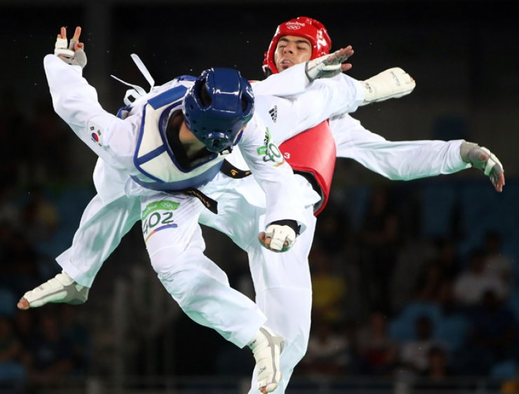 South Korea's Lee Dae-hoon, left, competes against Jaouad Achab of Belgium in the men's -68kg taekwondo bronze medal contest at the Rio de Janeiro Olympics on Thursday. Lee defeated Achab 11-7. / Yonhap