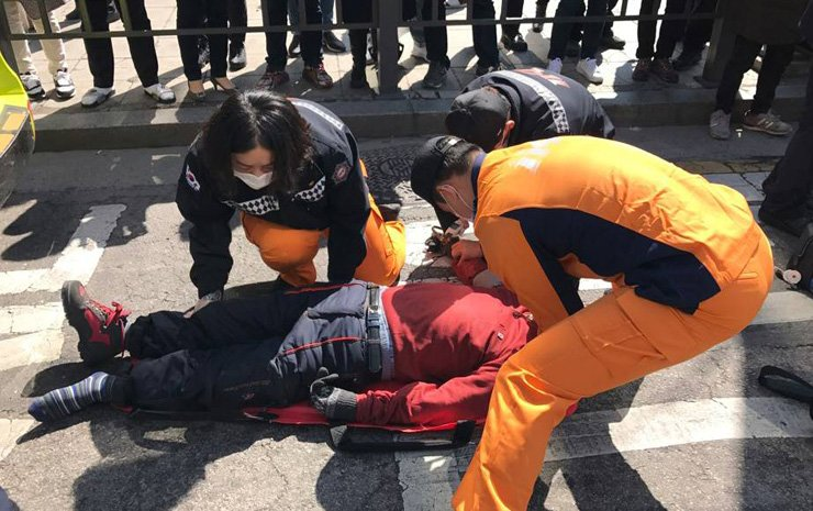 Emergency medical crews treat a pro-Park protester who collapsed after having breathing problems on a street in front of Anguk Station, near the Constitutional Court, Friday. / Yonhap