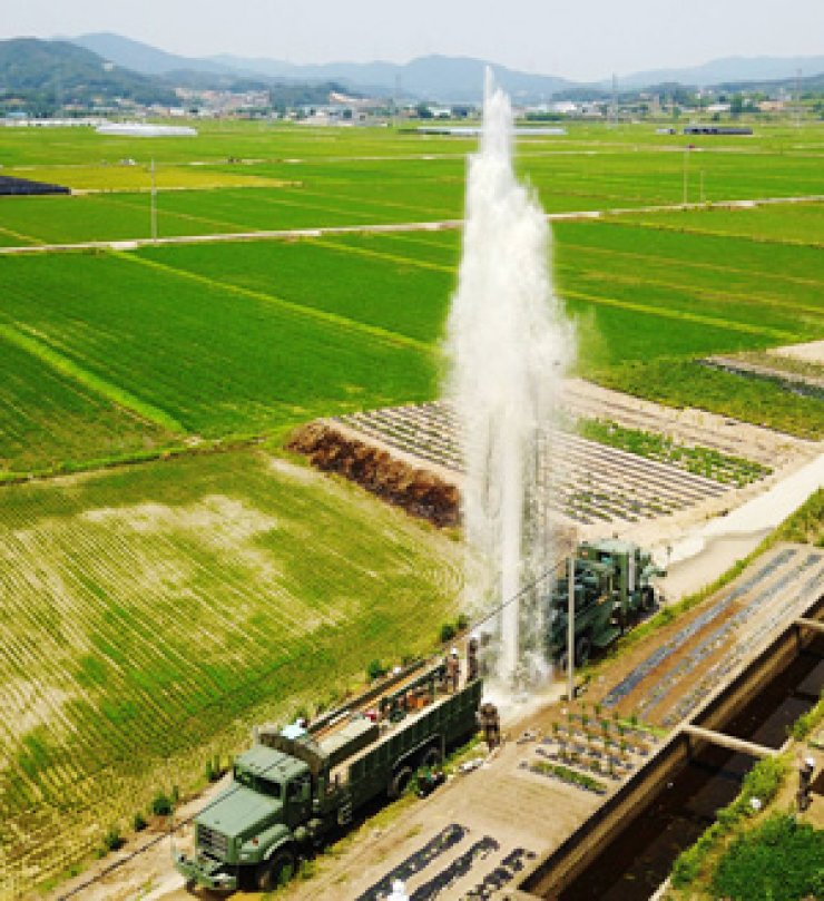 Water shoots from a tube well under construction in Bogae-myeon, Anseong, Gyeonggi Province, on June 19. The 55th Army Division used 200 vehicles and 400 soldiers to supply some 2,100 tons of water to drought-hit farms in five cities in the province, including Gwangju, Yeoju, Icheon and Yongin. / Yonhap