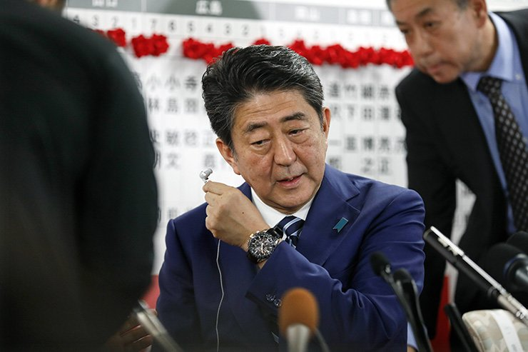 Japanese Prime Minister Shinzo Abe wears off earphone as he attends at headquarters of the ruling Liberal Democratic Party in Tokyo, Japan, Oct. 22, after close of vote of the Lower House election. / EPA-Yonhap
