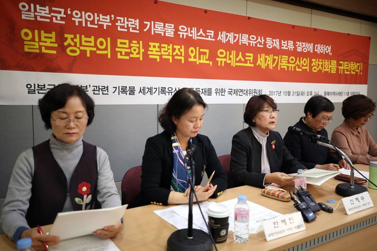 A group dedicated to telling the world about Japan's crime of forcing women into sexual slavery for its troops during World War II holds a press conference at the Northeast Asian History Foundation in Seodaemun-gu, Seoul, Oct. 31. It came the same day UNESCO's International Advisory Committee postponed listing the victims' records on its 'Memory of the World' register. The banner reads: 'We condemn the Japanese government's diplomatic efforts to undermine culture and politically influence UNESCO's Memory of the World listing.' / Yonhap