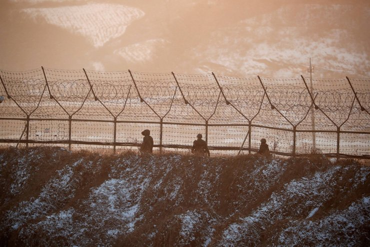 South Korean soldiers patrol along a barbed-wire fence near the militarized zone separating the two Koreas, in Paju, South Korea, Dec. 21. / Reuters