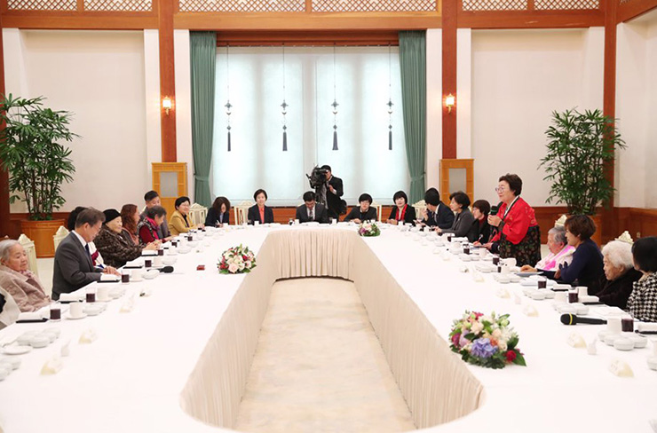 President Moon Jae-in talks with Kim Bok-dong, 90, a former wartime sex slave of the Japanese military, in her room at the Severance Hospital in Seoul, Thursday. The visit was preceded by his lunch with other former 'comfort women' and their supporters at the presidential office, Cheong Wa Dae. / Yonhap