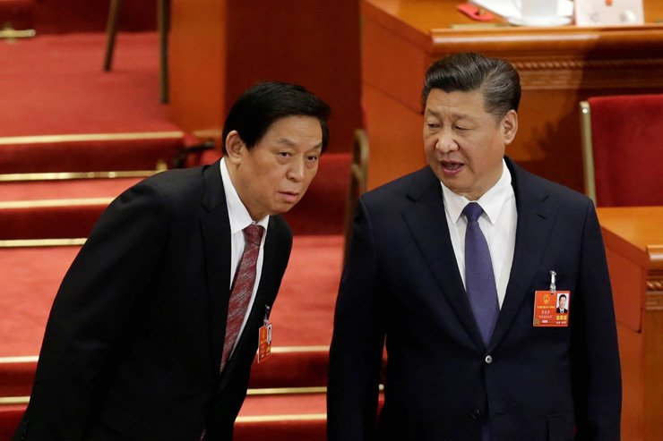 Chinese President Xi Jinping speaks with Chinese Politburo Standing Committee member Li Zhanshu at the third plenary session of the National People's Congress at the Great Hall of the People in Beijing, China on Mar. 11. / Reuters-Yonhap