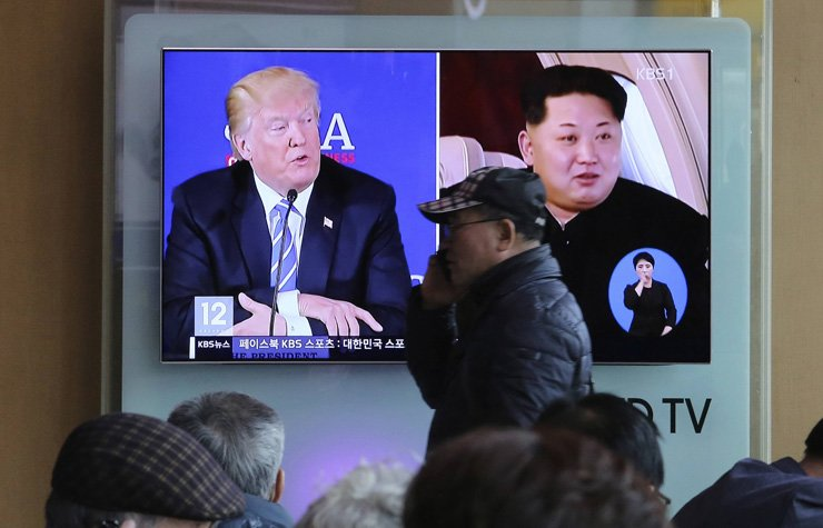 A man passes by a TV screen showing file footage of U.S. President Donald Trump, left, and North Korean leader Kim Jong-un during a news program at the Seoul Railway Station in Seoul, April 9. / AP-Yonhap