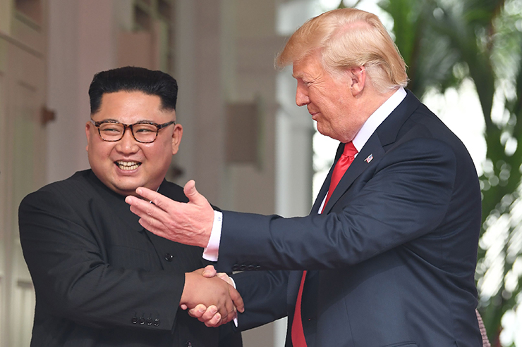 U.S. President Donald Trump (R) and North Korea's leader Kim Jong Un (L) walk toward one another at the start of their historic US-North Korea summit, at the Capella Hotel on Sentosa island in Singapore on June 12, 2018. AFP