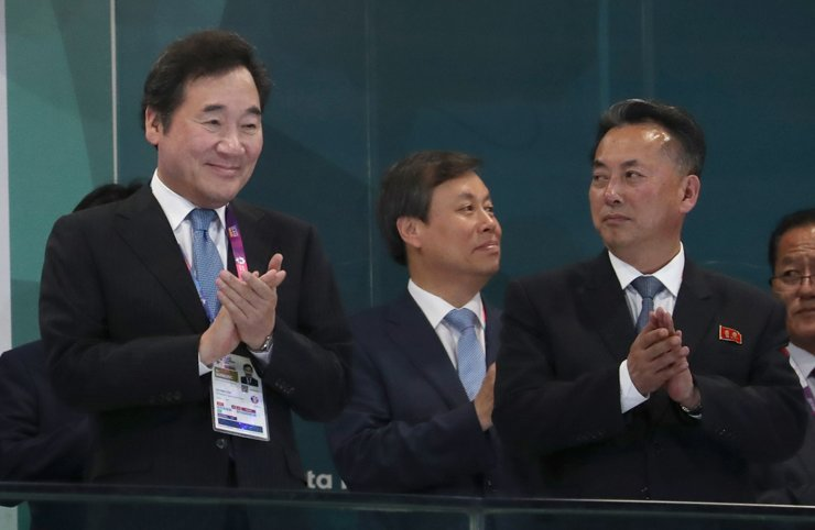 South Korean Prime Minister Lee Nak-yon, left, applauds with North Korean Deputy Prime Minister Ri Ryong-nam during the opening ceremony of the 2018 Asian Games in Jakarta, Indonesia, Saturday. / Yonhap