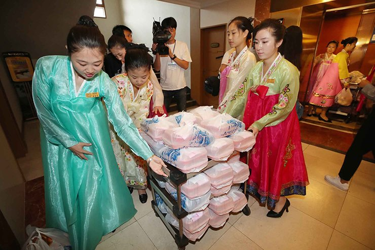 North Korean women carry lunch boxes to rooms where South and North Korean families hold individual meetings at the Diamond Mountain resort in North Korea, Tuesday, Aug. 21, 2018. For the first time in three years, elderly North and South Korean relatives separated during the chaos of the 1950-53 Korean War are meeting at the North's scenic Diamond Mountain, where they'll embrace their loved ones after decades apart. Korea Pool