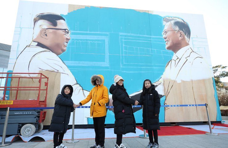 People pose in front of a giant poster of President Moon Jae-in and Nort Korean leader Kim Jong-un near Cheong Wa Dae, Dec. 7. / Yonhap