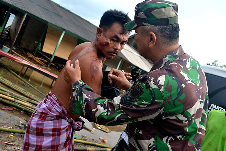A soldier examines as he takes care of a local resident who was injured following a tsunami which hit at Tanjung Lesung district in Pandeglang, Banten province, Indonesia, December 23, 2018. Reuters