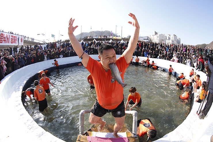 A festival visitor celebrates after attending bare hand fishing in a frozen river during the Hwacheon Sancheoneo Ice Festival at Hwacheon-gun in Gangwon province, South Korea, 05 January 2019. EPA