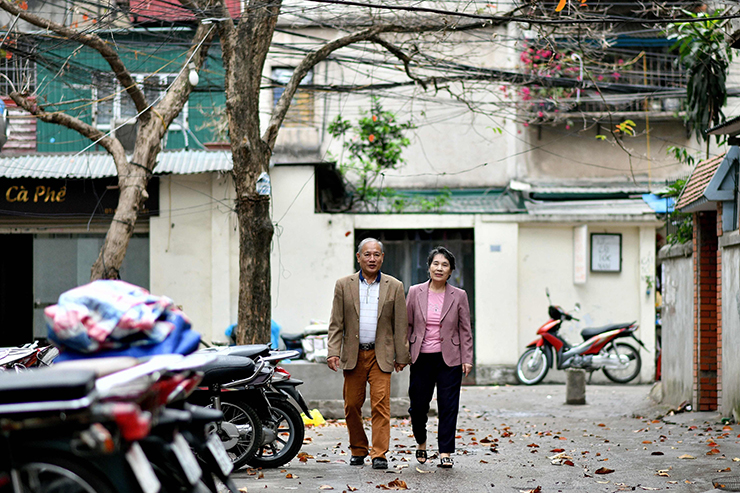 Vietnamese man Pham Ngoc Canh, (L), and his North Korean wife Ri Yong Hui pose together holding their wedding photograph outside their house in Hanoi on February 13, 2019. - A handkerchief, illicit letters and secret visits -- the first three decades of love between a Vietnamese man and his North Korean sweetheart were counted out in stolen moments and small tokens of devotion. AFP