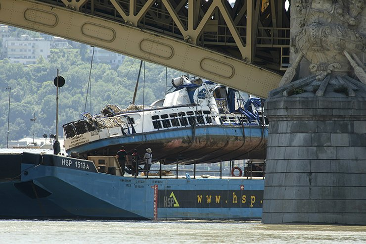 A crane places the wreckage of the sightseeing boat on a transporting barge at Margaret Bridge, the scene of the fatal boat accident in Budapest, Hungary, Tuesday, June 11, 2019. The Hableany sightseeing boat carrying 33 South Korean tourists and two Hungarian staff was crashed by a large river cruise ship and sank in the River Danube on May 29. Seven tourists survived, twenty people died, eight persons are still missing. AP