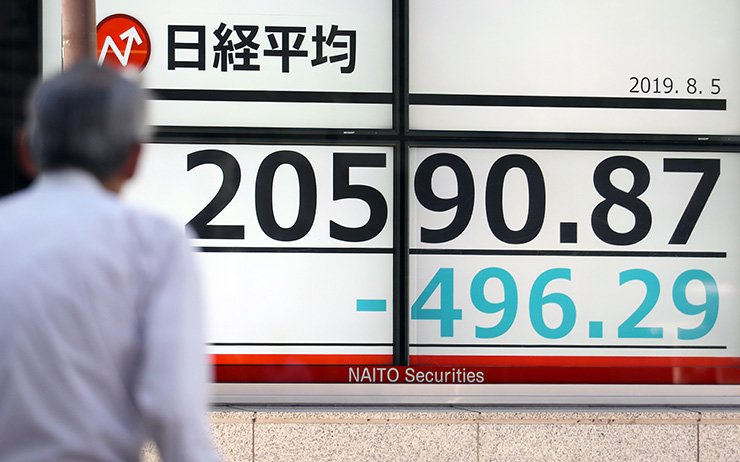 A pedestrian walks past a stock market indicator board in Tokyo, Japan, 05 August 2019. Following growing tensions between the USA and China and a stronger yen, Tokyo stocks lost more than two percent. The 225-issue Nikkei Stock Average dropped by 496.29 points, or 2.35 percent, to 20,590.87 during the morning trading session. EPA