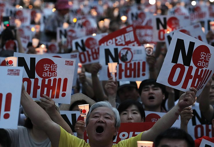 Protesters shout slogans as they hold signs and candles during a rally denouncing Japanese Prime Minister Shinzo Abe and also demanding the South Korean government to abolish the General Security of Military Information Agreement, or GSOMIA, an intelligence-sharing agreement between South Korea and Japan, near the Japanese embassy in Seoul, South Korea, Saturday, Aug. 10, 2019. The letters read 'No Abe.'  AP