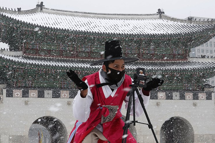 A man dressed in South Korean traditional 'Hanbok' attire wears a face mask in the snow as he gestures to take photos at the Gyeongbok Palace, the main royal palace during the Joseon Dynasty in Seoul, South Korea, Monday, Feb. 17, 2020. Chinese authorities on Monday reported a slight upturn in new virus cases and hundred more deaths for a total of thousands since the outbreak began two months ago. AP