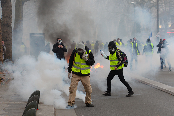 A 'Yellow vest' (gilets jaunes) anti-government demonstrator holds up the French flag as he stands infront of a fire during protests in the western French city of Bordeaux on Dec. 29. Police fired tear gas at 'yellow vest' demonstrators but the turnout for round seven of the popular protests that have rocked France appeared low. The yellow vests movement originally started as a protest about planned fuel hikes but has morphed into a mass protest against President's policies and top-down style of governing. AFP