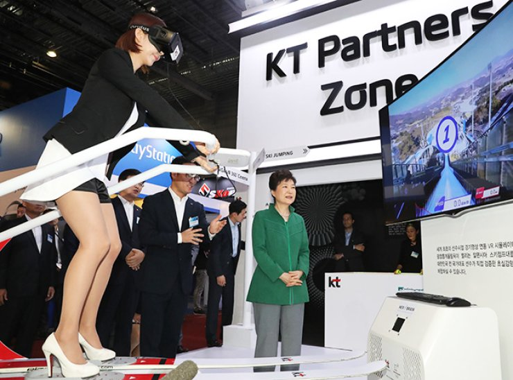 President Park Geun-hye tours the KT booth while a company employee uses a virtual reality (VR) simulator for ski jumping during the Korea VR Festival at Nuridream Square, western Seoul, Oct. 7. / Courtesy of KT