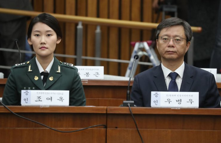 People involved in the Park Geun-hye scandal sit to be questioned by lawmakers in a parliamentary investigation of the scandal, Thursday. From left, Cho Yeo-ok, an army captain who worked as a nurse at the presidential office at the time of the Sewol disaster; and Woo Byung-woo, former presidential secretary. / Yonhap
