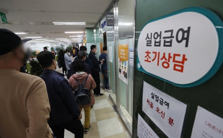 People line up in front of an office run by the Ministry of Employment and Labor in Seoul to apply for unemployment benefits. The amount of state allowances paid to those unemployed or seeking jobs soared to a record high in March due mainly to the negative economic impact from the COVID-19 pandemic. Yonhap