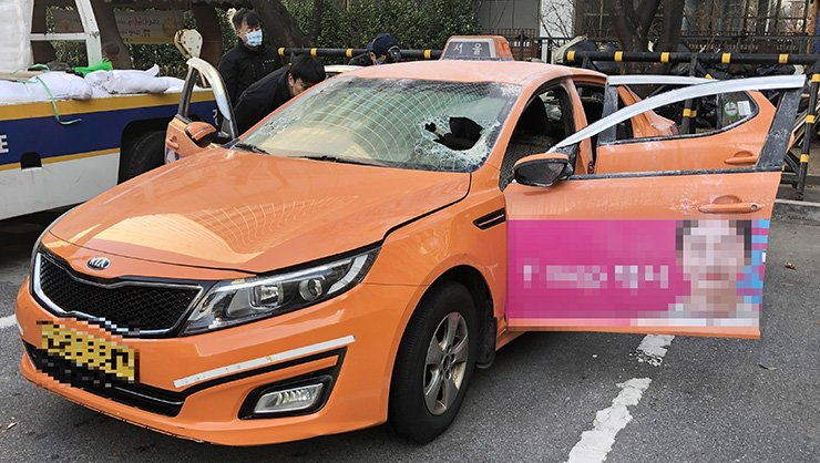 Investigators look into the car of the taxi driver after he set himself on fire in protest of the launch of Kakao's ride-sharing service, at the Yeongdeungpo Police Station in Seoul, Monday. Yonhap