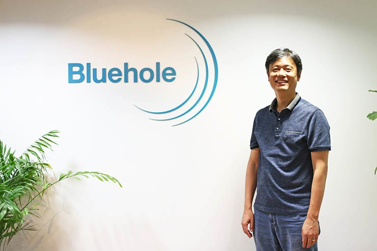 Bluehole founder Chang Byung-gyu poses beside the company's logo at his office in Pangyo, Gyeonggi Province, Tuesday. / Korea Times photo by Yoon Sung-won
