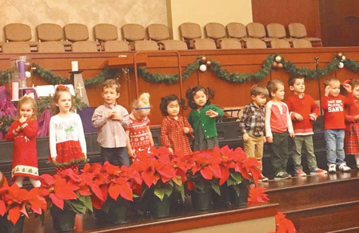 Ann and Ellen, fifth and sixth from left, stand on stage for their preschool's Christmas performance as they wave to familiar faces. / Courtesy of Jane Han
