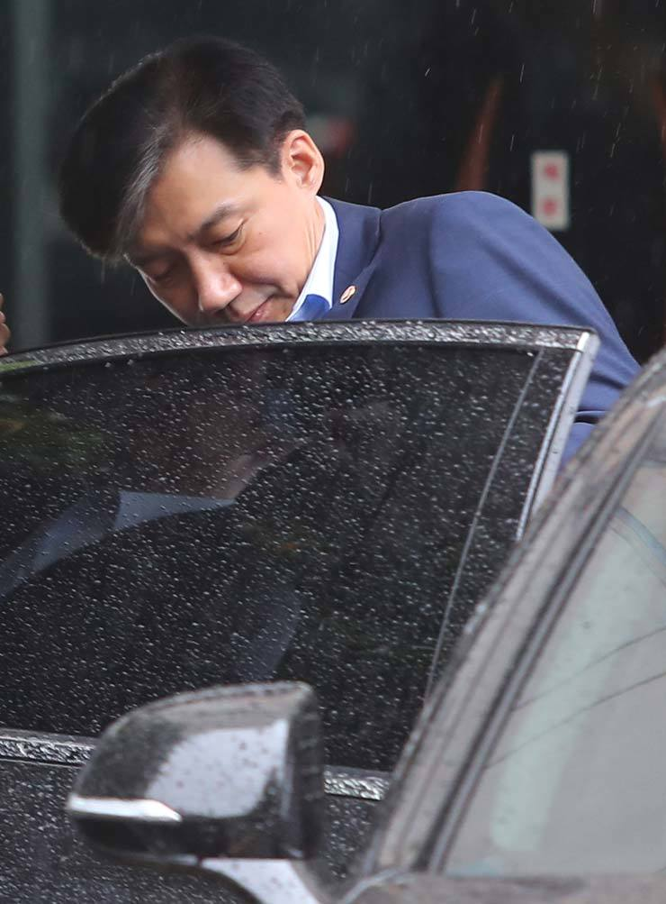 Justice Minister Cho Kuk gets in a car in front of his house in southern Seoul, Monday, to go to work amid a prolonged prosecution probe into alleged misconduct surrounding his family. / Yonhap