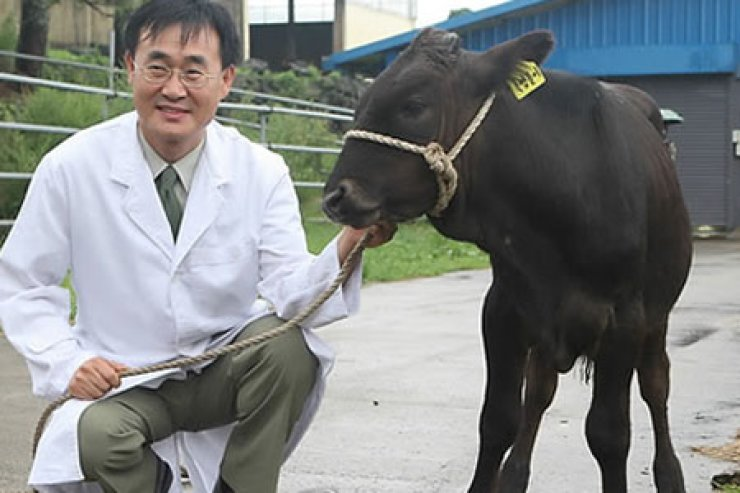 Prof. Park Se-pill of Jeju National University poses with a newborn cloned black cow in 2009. /  Korea Times file