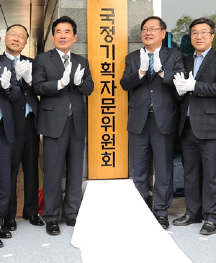 Rep. Kim Jin-pyo of the ruling Democratic Party of Korea, second from left, chairman of a presidential advisory committee tasked to map out a five-year policy roadmap, applauds along with other committee members during a launch ceremony for the committee at the training center for the Financial Supervisory Service in Seoul, Monday. / Yonhap