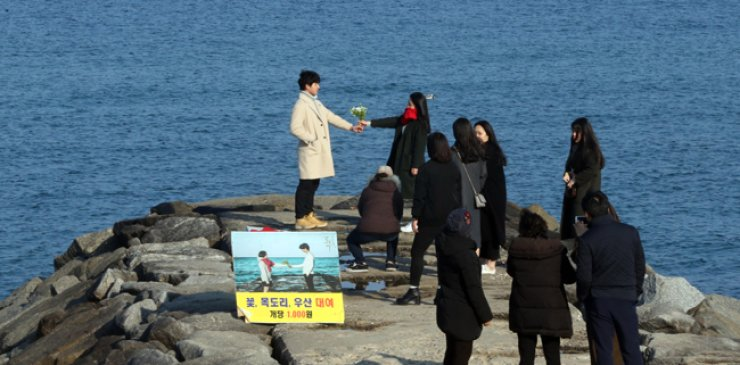 Tourists take photos on a breakwater in Jumunjin Gangneung, Gangwon Province, Jan. 2, a filming site for tvN's popular drama 'Guardian: The Lonely and Great God.' The place and the drama's other filming locations have become hot destinations for drama fans. / Yonhap