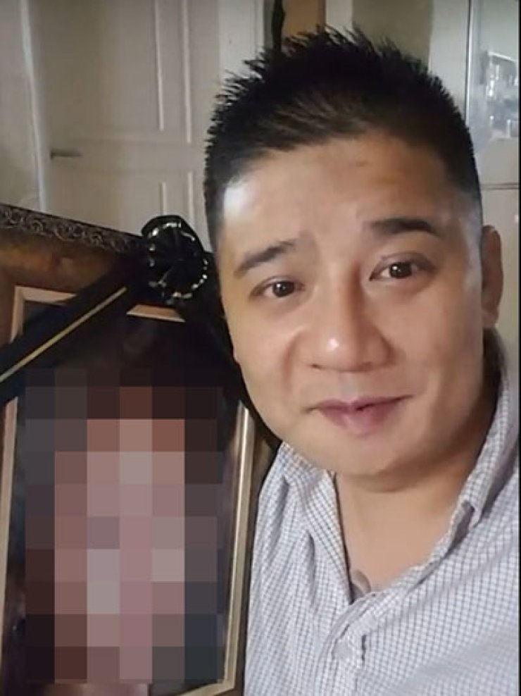 Murder suspect Lee Young-hak posted a YouTube video, in which he sings the song 'The Love' while holding his dead wife's photo, days after she committed suicide on Sept. 5. He is under investigation for the death of a friend of his 14-year-old daughter on Oct. 1 and abandoning her body in the mountains of the remote eastern county of Yeongwol. His daughter allegedly helped him during the murder. / Yonhap