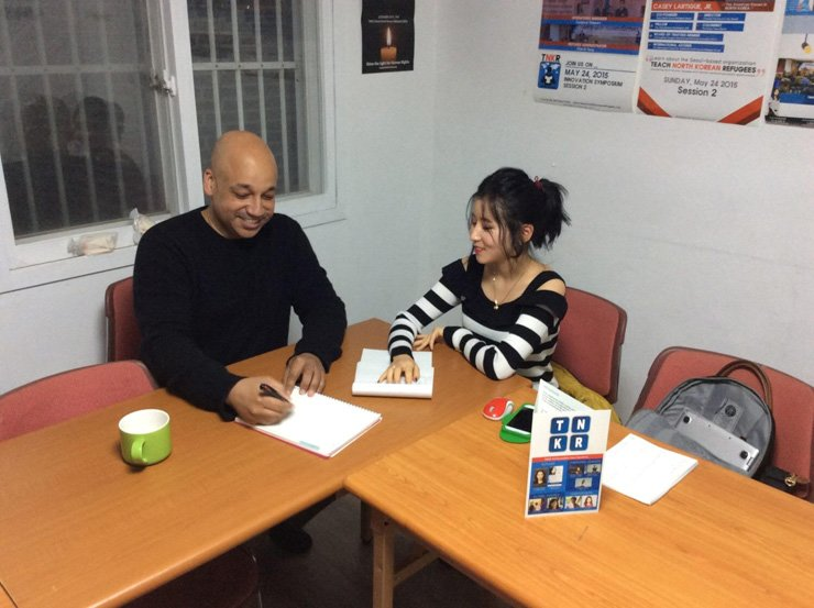 Tech North Korean Refugees (TNKR) co-founder Casey Lartigue, left, is tutoring a North Korean refugee at the TNKR Study Center in Seoul in this recent photo. / Courtesy of Casey Lartigue