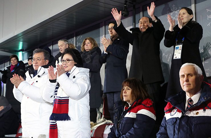 President Moon Jae-in, left in the front row, gives a standing ovation with other dignitaries, including North Korean leader Kim Jong-un's sister Kim Yo-jong, right in the back row, and the North's nominal head Kim Yong-nam, second from right in the back row, as North and South Korean athletes march together under the 'unification flag' at the opening ceremony of the PyeongChang Winter Olympics, Friday. U.S. Vice President Mike Pence, right in the front row, remains seated. / Yonhap