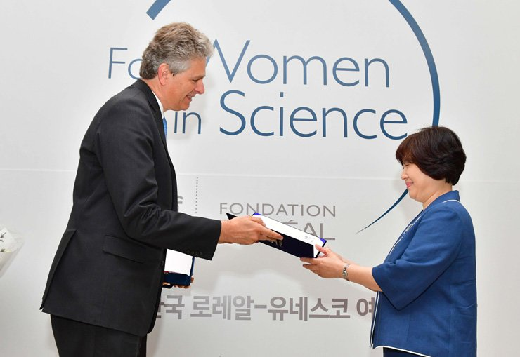 Son Young-sook, a professor of genetic engineering at KyungHee University, receives the grand award from L'Oreal Korea CEO Yann Le Bourdon during a ceremony at Seoul National University, June 27. / Courtesy of L'Oreal Korea