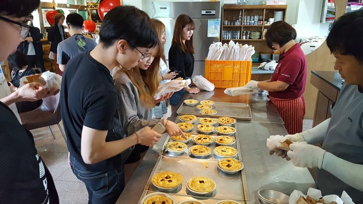 Tourists purchase apple pies made of apples and other local ingredients at a culinary experience center in Yesan, South Chungcheong Province, June 3, 2016. The ministry has been organizing food tour programs for both Koreans and non-Koreans to promote iconic dishes from each municipality and to bolster the consumption of agricultural products. / Courtesy of Ministry of Agriculture, Food and Rural Affairs
