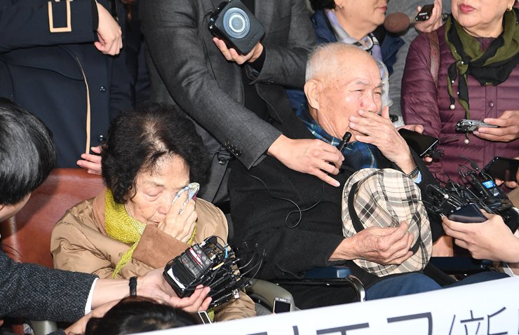 Lee Chun-sik, right, the last surviving plaintiff in a compensation lawsuit filed by Korean forced laborers against Nippon Steel, sheds tears outside the Supreme Court in southern Seoul, after winning the suit, Tuesday. On the left is the widow of Kim Kyu-soo, one of the deceased plaintiffs. / Korea Times photo by Shin Sang-soon